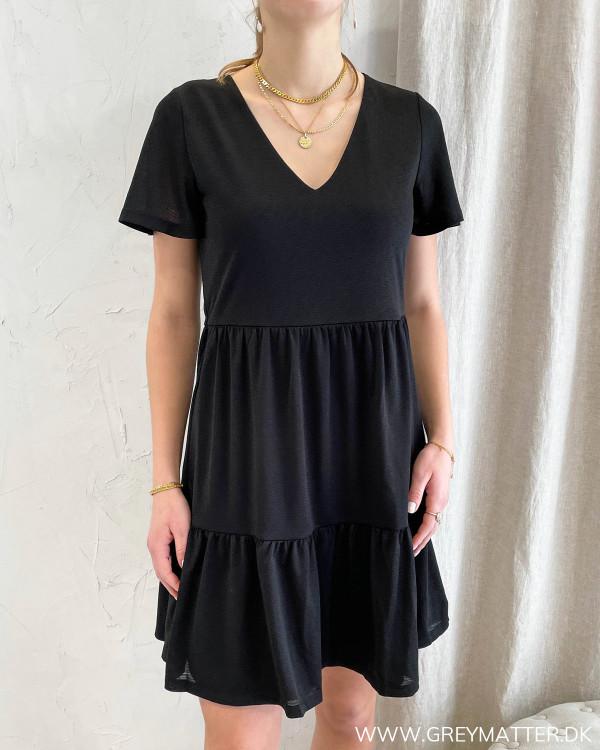 Sort kjole med flæsedetaljer
