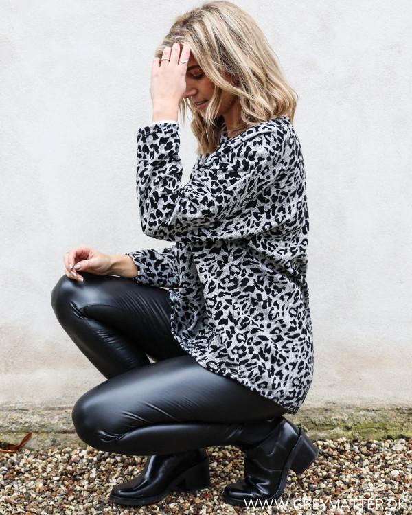 Leopard sweatshirt stylet med sorte leggings og høje sorte støvler