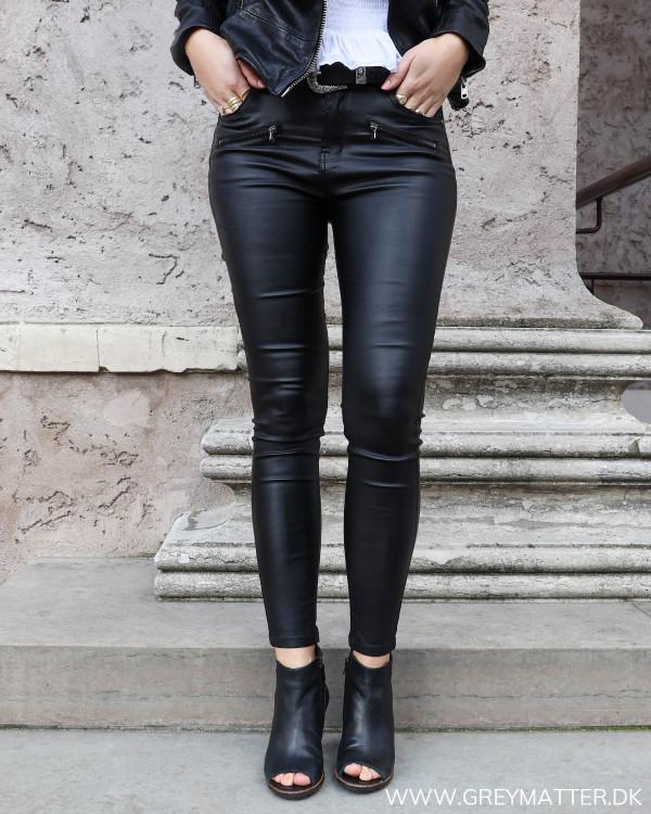 Coatede bukser med lynlåse set forfra