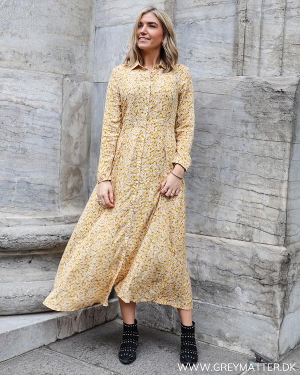 Lang kjole i gule farver med blomsterprint set forfra