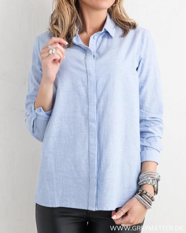 Pieces skjorte i lyseblå set forfra med fokus på knappelukning