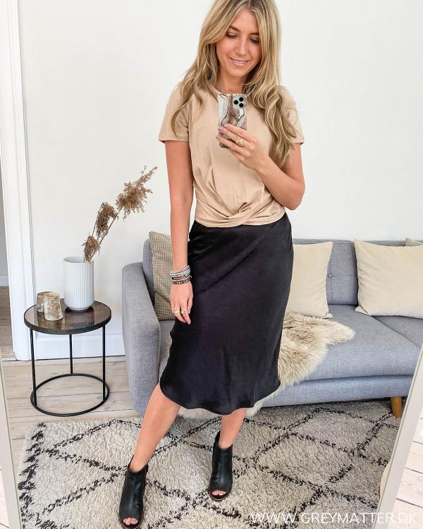 Sort nederdel stylet med kort beigefarvet t-shirt