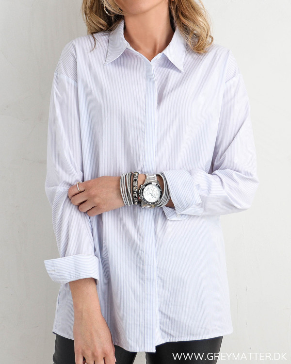 Klassisk skjorte til damer med lyseblå striber, set forfra
