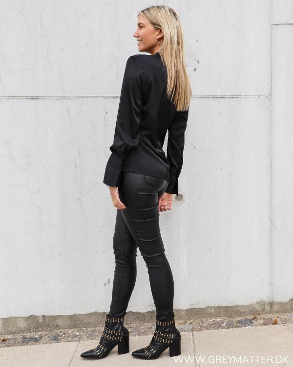 Sort enkel bluse fra Karmamia stylet med høje støvler og coatede bukser